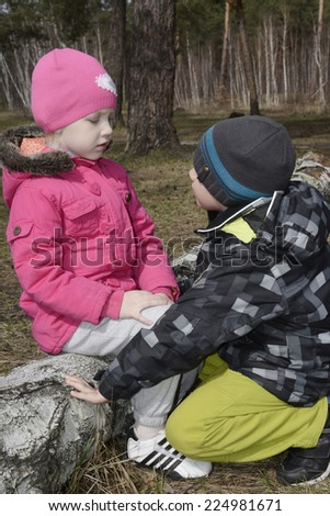 In the spring forest small boy apologizing to the little girl who is sitting on a log and looking at him with displeasure. - stock photo