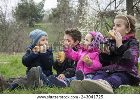 In the spring of four small child sitting in the meadow on the grass and eat cookies. - stock photo