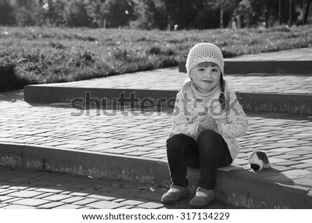 In the spring on the street sitting on the steps of a little girl with a toy dog. - stock photo