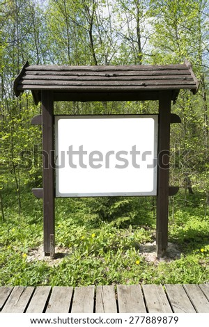 In the spring wood there is a wooden stand with information. Empty area isolated with patch