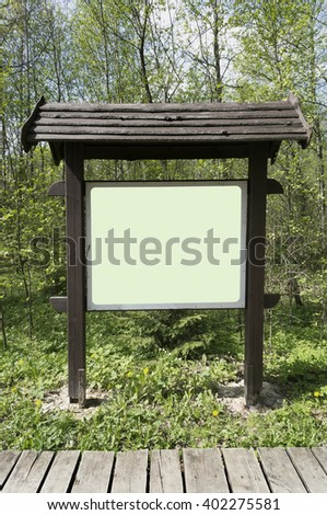 In the spring wood there is a wooden stand with information. Empty green area isolated with patch