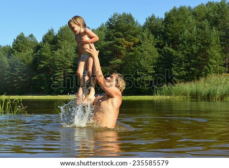 In the summer, bright sunny day, the little girl and man is bathed dives,run, jumps into the river. Beside him spray.  - stock photo