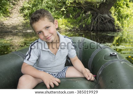 In the summer on the river a  curly-haired boy sitting in a rubber boat near water lilies. - stock photo