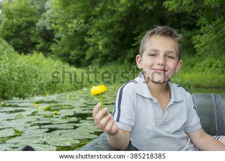 In the summer on the river curly-haired boy sitting on a rubber boat and holding a water lily. - stock photo