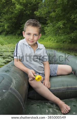 In the summer on the river curly little boy sitting on a rubber boat near water lilies and holding a flower in her hand.. - stock photo