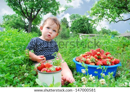 In the summer, the garden beds near the little girl is sitting, and near it is a full circle of strawberries - stock photo