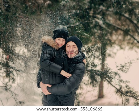 in the winter a lot of snow in the park father and son in black jackets and hats