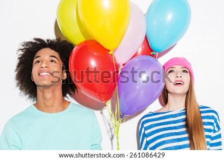 In their own colorful world. Funky young couple holding balloons and looking up while standing against white background - stock photo