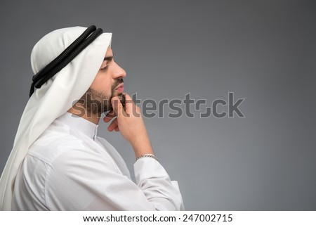 In thoughtful mood.  Side view portrait of young handsome Arab business man in head cloth looking at copy space with his hand on chin while standing isolated on grey background  - stock photo