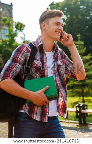 In touch with his friends. Handsome male student talking on the mobile phone and smiling while walking outdoors - stock photo