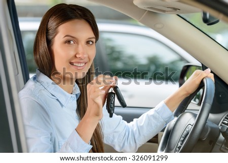 In whirlwind of life. Pretty smiling vivacious beautiful young woman holding keys and keeping wheel while  driving a car. - stock photo