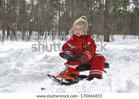 In winter, a bright sunny day in the forest boy is sitting on a sled and smiling. - stock photo