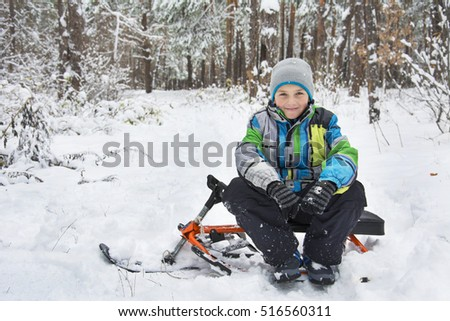 In winter, the snow-covered forest pine boy sitting on a sledge.