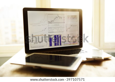 inancial graph on the screen of the laptop and tablet workplace  - stock photo