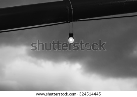 Incandescence bulbs with noise and grain on sky background, in Black & White tone, shallow depth of field, selective focus (detailed close-up shot) - stock photo