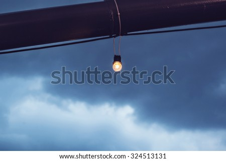 Incandescence bulbs with noise and grain on sky background, in vintage tone color style, shallow depth of field, selective focus (detailed close-up shot) - stock photo