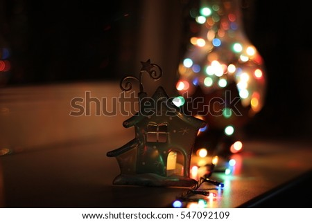 Incandescent lamp full of lights of garland and little statuette of house with a candle/ low depth of field, bokeh