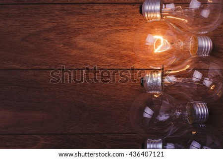 Incandescent lamps glowing on wooden background.  Concept for leadership. Concept for idea. Concept for solution. Concept for energy.