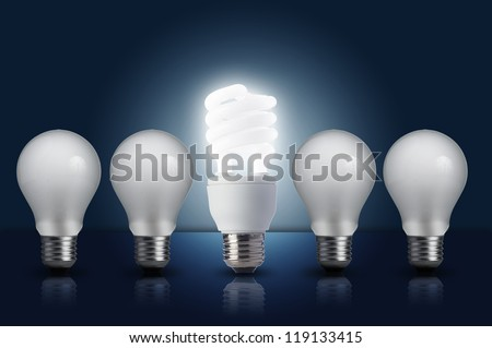 Incandescent light bulb in a row with middle fluorescent light bulb on. Concept for energy conservation - stock photo