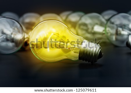 Incandescent light bulbs on dark surface with the center one lighting - stock photo