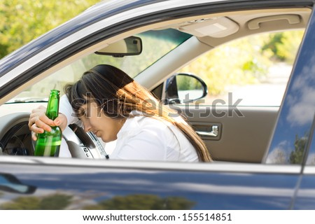 Incapacitated drunk woman driver leaning her head on the steering wheel while still gripping her bottle of booze - stock photo