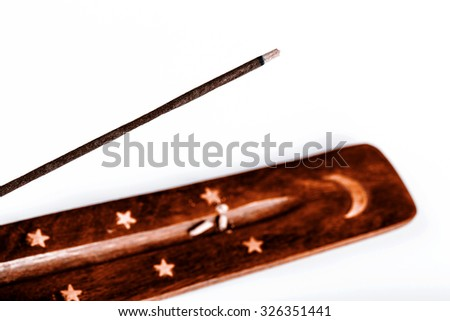 Incense stick on a wooden support with smoke on a white background - stock photo