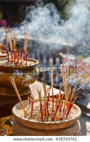 Incense Sticks Burning with Smoke at Archaeological Site at Kamphaeng Phet Historical Park. Kamphaeng Phet Province, Thailand - stock photo