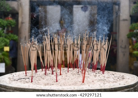 Incense sticks on joss stick pot are burning and smoke use for pay respect to the Buddha. - stock photo