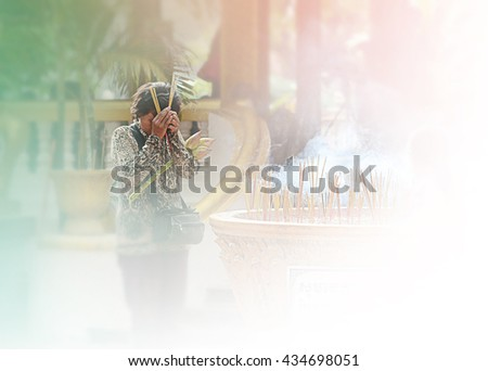 Incense sticks on joss stick pot are burning and smoke use for pay respect to the Buddha, Incense sticks in woman hand and smoke use for pray respect to the Buddha in Buddhism life. - stock photo