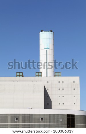 Incineration plant with chimney against blue sky - stock photo