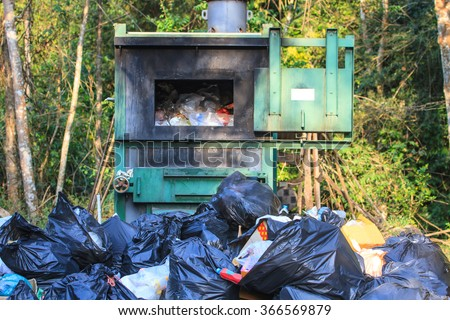 Incinerator in national park with garbage background - stock photo