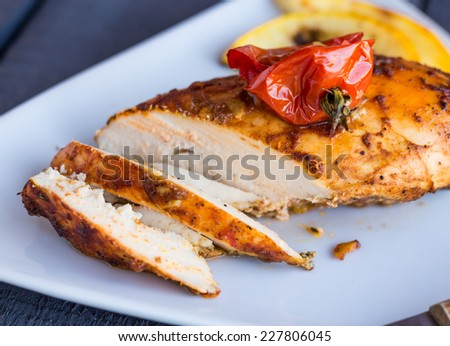 incision baked chicken in a spicy curry sauce with vegetables,on a white plate - stock photo