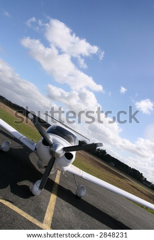 Inclined front view of a white plane on the runway - stock photo