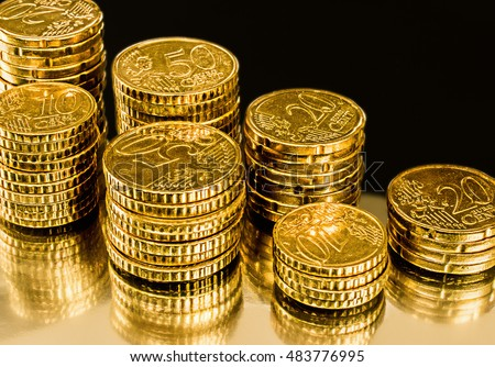 Income and profits concept. Stacks of gold money coins. Isolated on black and gold shiny background.