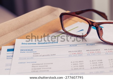 Income statement letter on brown envelope and eyeglass, business concept; document is mock-up - stock photo