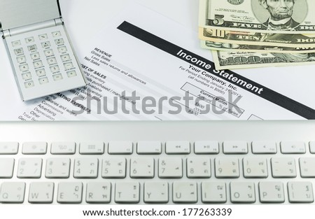 income statement report with calculator, key broad and usd money for business - stock photo