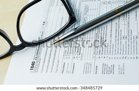Income tax form with pen and eyeglasses