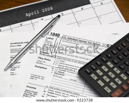 Income tax forms with a pen and calculator on a table. - stock photo