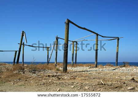 Incomplete and abandoned construction of a house on the beach over cloudless sky - stock photo