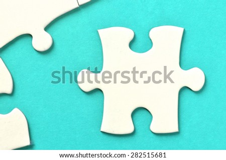 Incomplete puzzle on turquoise background
