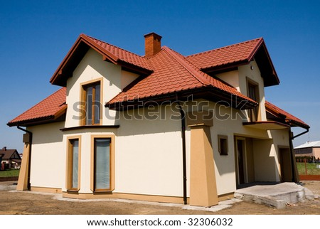 Incomplete single family small yellow house against blue sky - stock photo