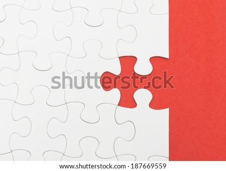 Incomplete white puzzle with red color background with copyspace. - stock photo