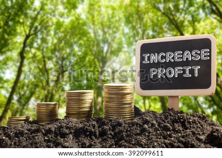 Increase Profit - Financial opportunity concept. Golden coins in soil Chalkboard on blurred natural background - stock photo