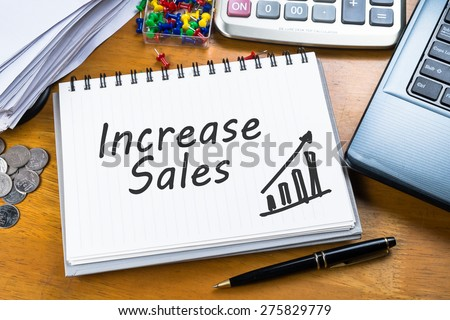 Increase Sales on notebook with part of laptop, receipts and calculator - stock photo