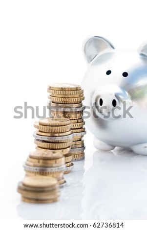 Increasing height stacks of coins with silver piggy bank in background, isolated on white.