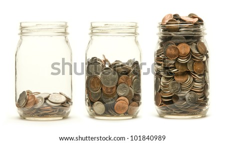 Increasing numbers of American coins in a three glass jars against a white background - stock photo