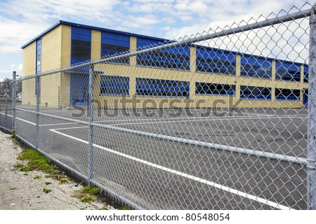 Increasing security of an old small school by restricting access with a gate or wire mesh fence courtyard asphalt playground. - stock photo