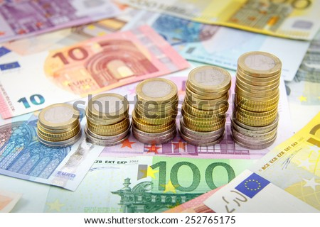 Increasing stacks of euro coins on euro banknotes - stock photo