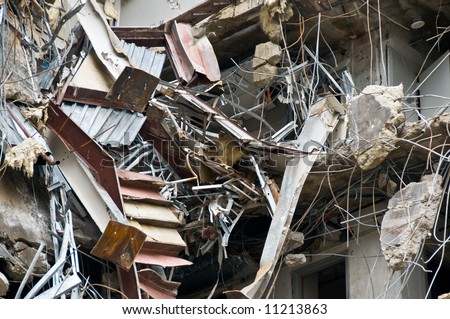 incredible building wreckage including hanging stairs, doorways, concrete, and rebar - part of series - stock photo