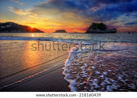 Incredible ocean bay sunset with spectacular clouds distant cliffs and breaking wave - stock photo